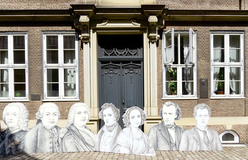 Ausschnitt historische Häuser mit gezeichneten Porträts historischer Gestalten