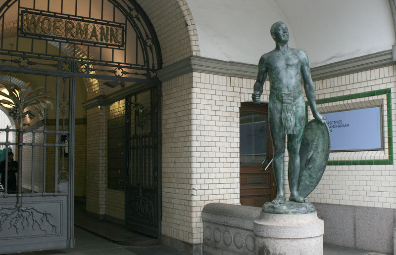 Statue eines afrikanischer Mannes mit Speer und Lendenschurz vor dem Afrikahaus