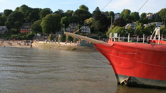 Elbstrand mit rotem Holzschiff